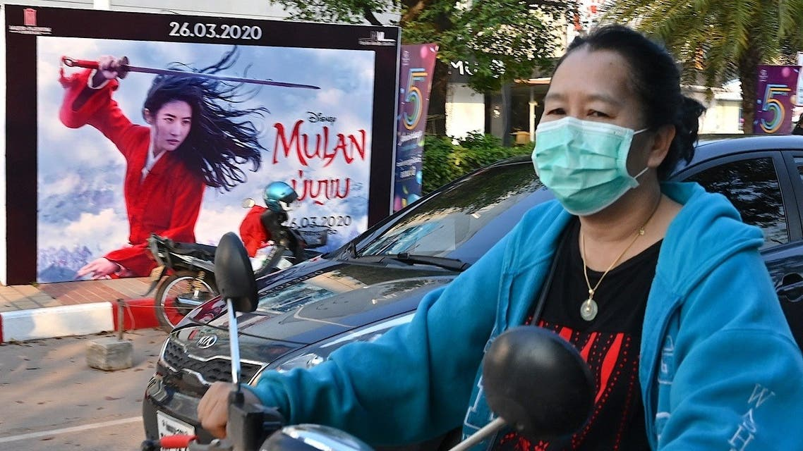 A woman, wearing a facemask amid concerns about the spread of the COVID-19 novel coronavirus, rides a motorcycle past a poster for the Disney film Mulan in Vientiane on March 11, 2020. (Mladen Antonov/AFP)