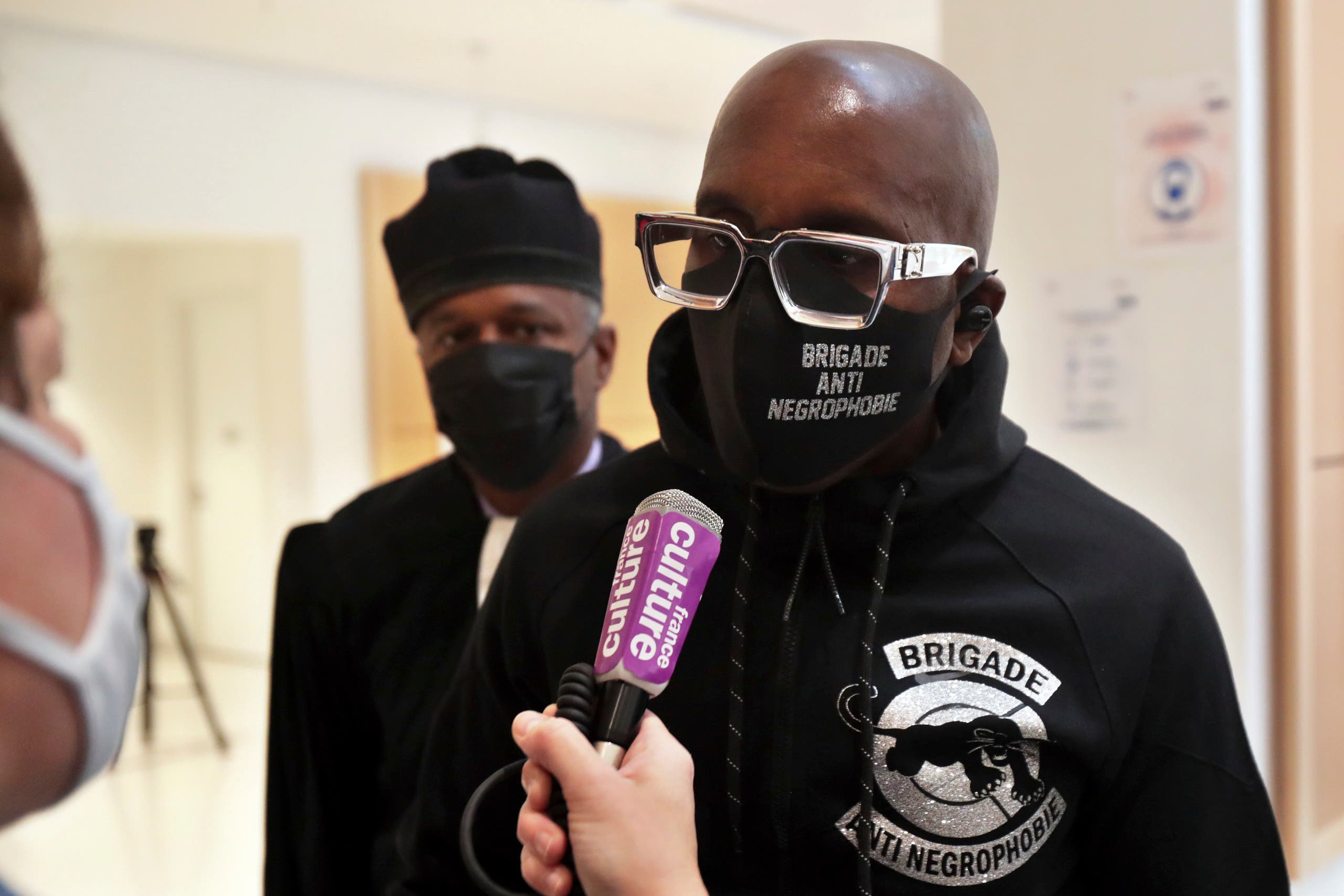 An activist from a group called the Anti-Negrophobia Brigade, Franco Lollia, wears a face mask reading Anti-Negrophobia Brigade as he talks to media at the Paris courthouse, in Paris, May 10, 2021. (AP)