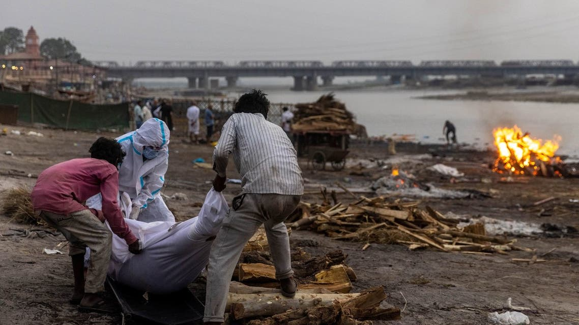 People place the body of a man who died from the coronavirus disease (COVID-19), on a pyre before his cremation on the banks of the river Ganges at Garhmukteshwar in the northern state of Uttar Pradesh, India, May 6, 2021. (Reuters)