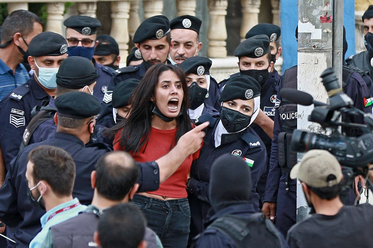 Police members restrain a demonstrator during a protest in solidarity with the Palestinian people near the Israeli embassy in Jordan's capital Amman on May 9, 2021. (Khalil Mazraawi/AFP)
