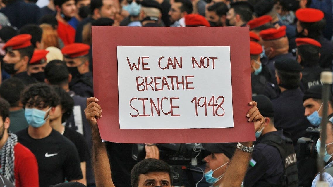 """A man holds up a sign reading in English """"we can not breathe since 1948"""" during a protest to express solidarity with the Palestinian people near the Israeli embassy in Jordan's capital Amman on May 9, 2021. (Khalil Mazraawi/AFP)"""