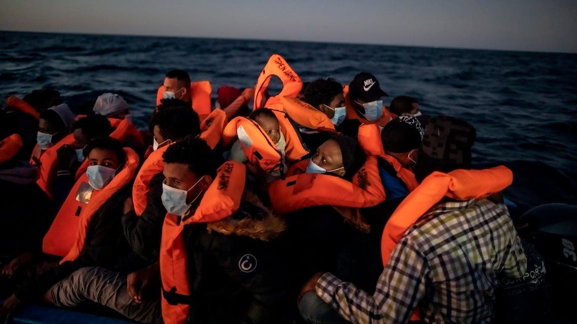Migrants and refugees from different African nationalities wait for assistance from aid workers of the Spanish NGO Open Arms on an overcrowded rubber boat in the Mediterranean Sea, off the Libyan coast, Feb. 12, 2021. (AP/Bruno Thevenin)