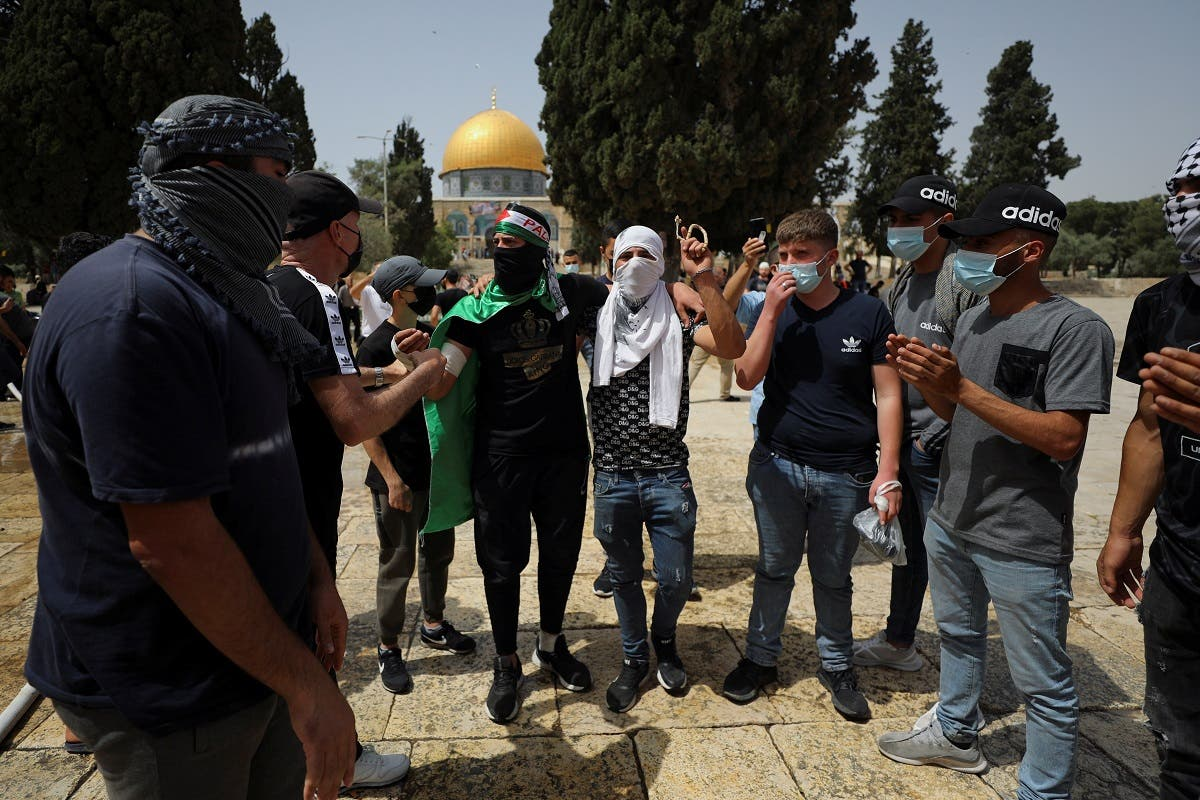 Palestinians stand together as the Dome of the Rock is seen in the background following clashes with Israeli police at the compound that houses al-Aqsa Mosque in Jerusalem's Old City on May 10, 2021. (Reuters)
