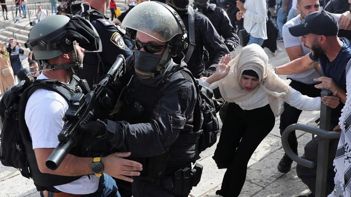 A Palestinian woman runs near Israeli security force members during scuffles amid Israeli-Palestinian tension as Israel marks Jerusalem Day, at Damascus Gate just outside Jerusalem's Old City on May 10, 2021. (Reuters)