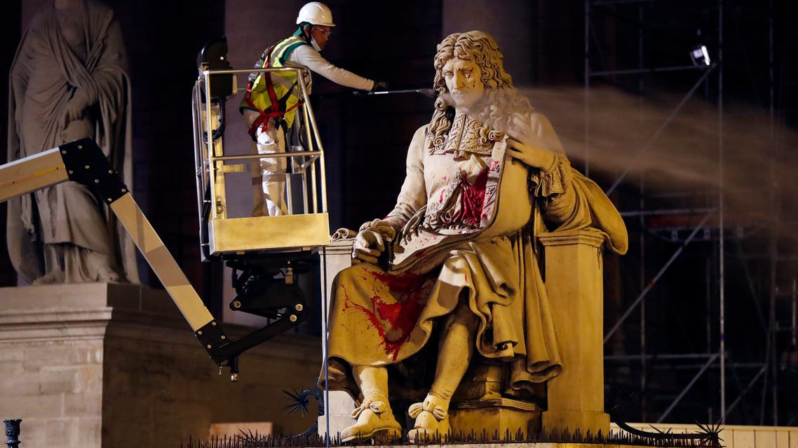 In this June 23, 2020 file photo, a worker from Paris' City Hall cleans the statue of Jean-Baptiste Colbert, in Paris. (AP)