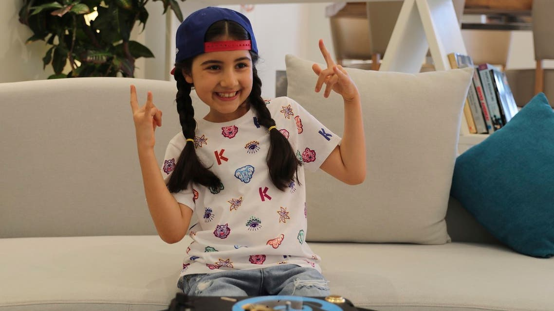 Michelle Rasul flashes a rockstar sign in the lobby of her apartment building in Dubai, United Arab Emirates, Sunday, May 9, 2021. Rasul, a 9-year-old girl from Azerbaijan who lives in Dubai, is scratching her way to the top as a DJ after competing in the DMC World DJ Championship. (AP)
