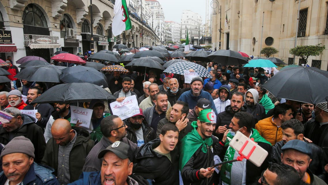 Demonstrators take cover from rain under umbrellas as they march during a protest demanding political change, in Algiers, Algeria April 16, 2021. (Reuters)