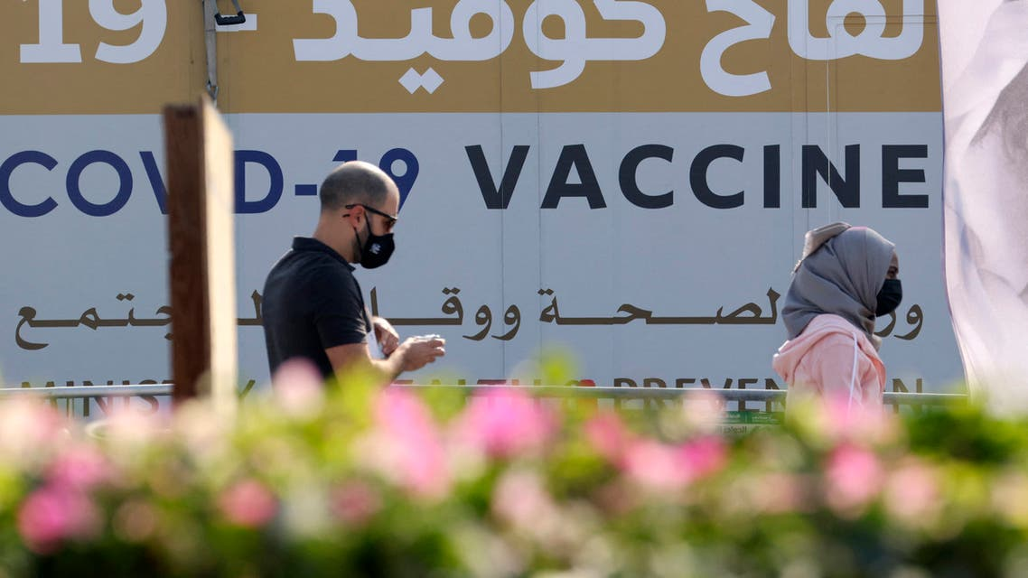 A man and a woman walk past a huge health ministry COVID-19 vaccines announcement outside a medical centre in Dubai on February 16, 2021, as the Gulf emirates goes ahead its vaccination effort. The UAE, home to a population of around 10 million, has administered some 4.6 million doses of vaccine, making it the second-fastest per capita delivery in the world, after Israel. (File photo: AFP)