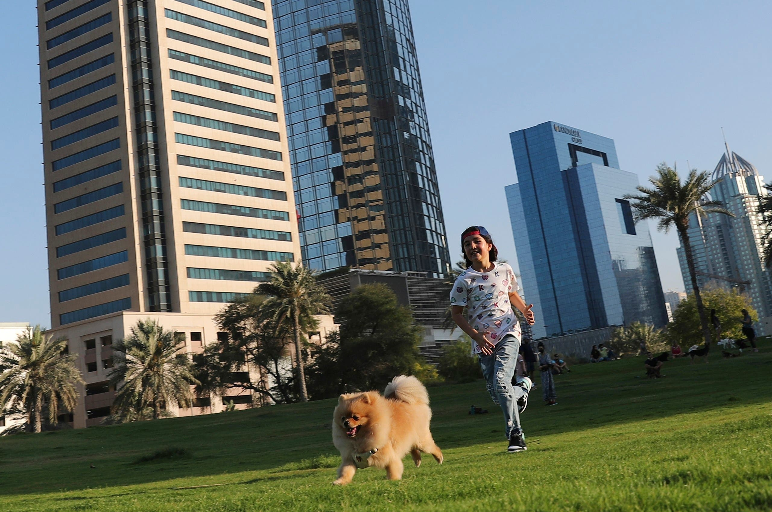 Michelle Rasul chases a friend's dog at a park near her house in Dubai, United Arab Emirates, Sunday, May 9, 2021. Rasul, a 9-year-old girl from Azerbaijan who lives in Dubai, is scratching her way to the top as a DJ after competing in the DMC World DJ Championship. (AP)