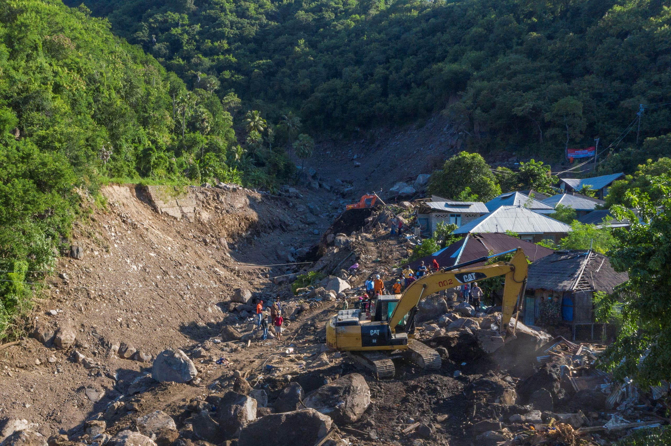 An aerial picture shows an excavator search for a body at an area affected by landslides triggered by tropical cyclone Seroja in Lembata, East Nusa Tenggara province, Indonesia April 10, 2021. (Reuters)