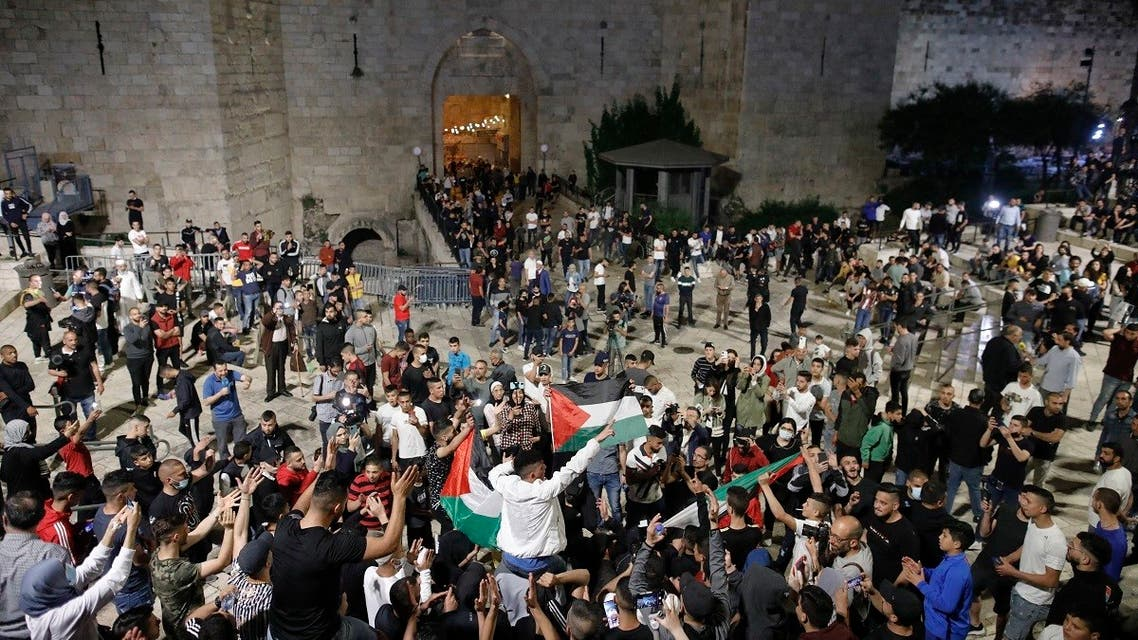 Palestinian protesters raise national flags as they gather near the Damascus Gate in Jerusalem's Old City, on April 25, 2021. (AFP)