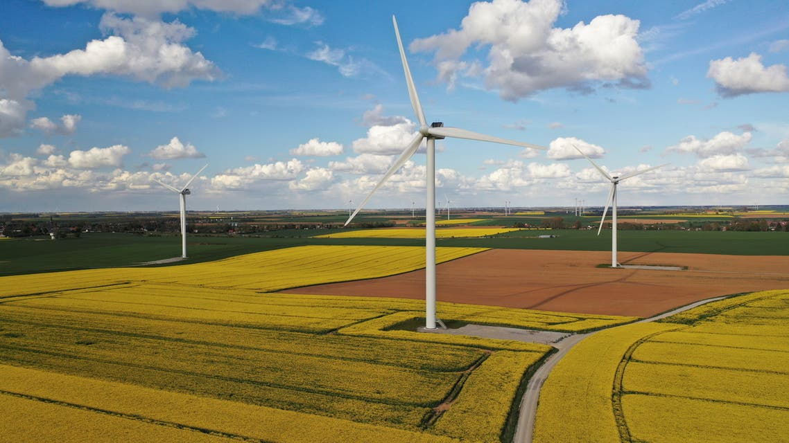 An aerial view shows power-generating windmill turbines in the middle of rapeseed fields, in Beauvois en Cambresis, France, May 5, 2021. Picture taken with a drone. (Reuters)