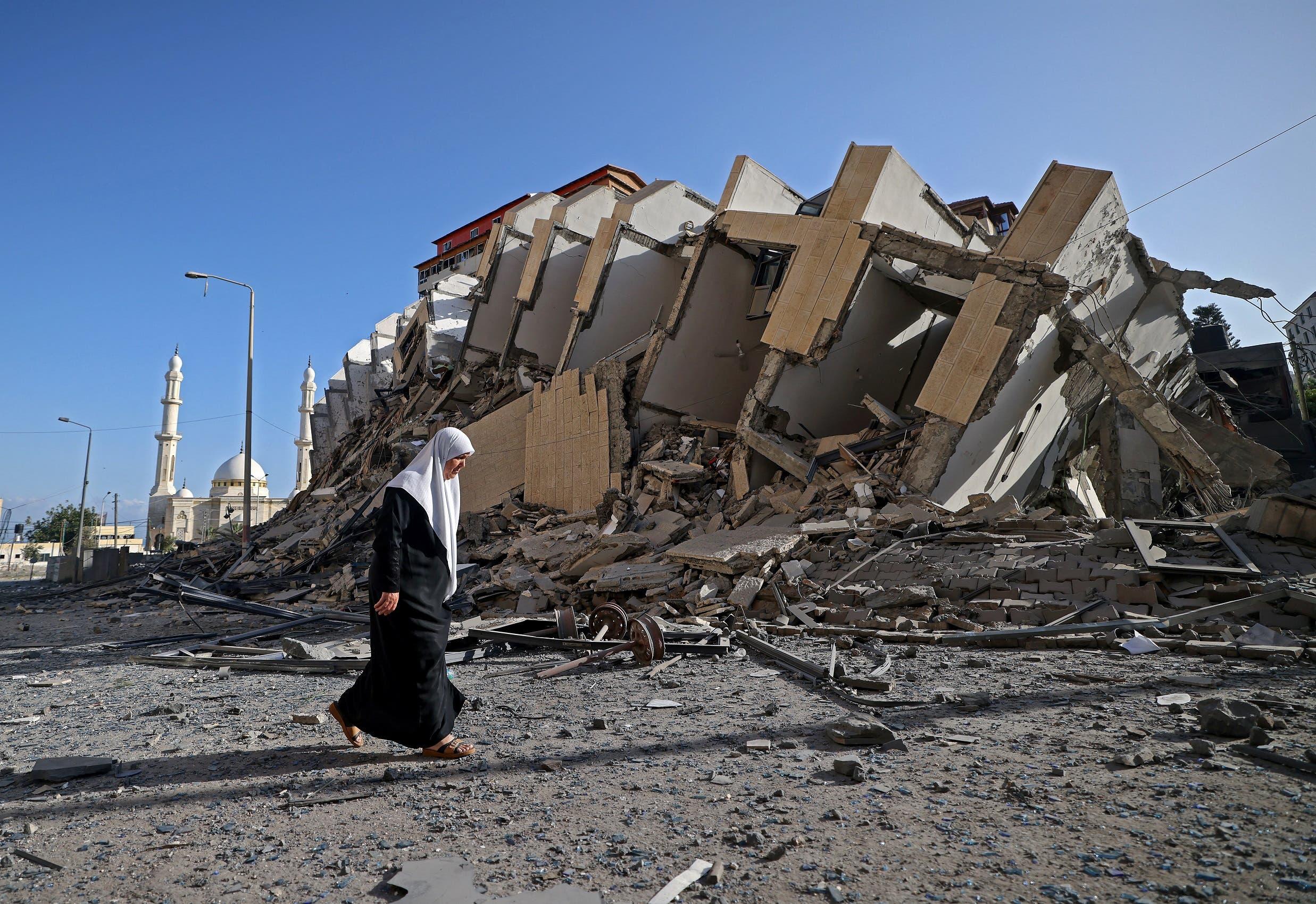 سيدة تمر قرب مبنى مهدّم في غزة