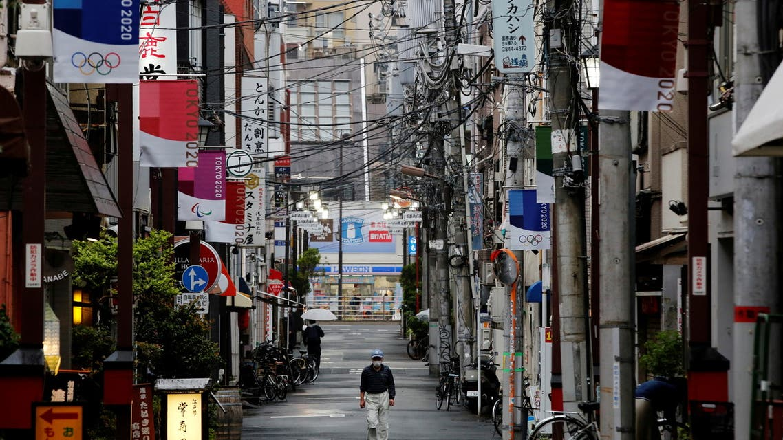 A man wearing a protective face mask, amid the coronavirus disease (COVID-19) pandemic, walks in a local shopping street decorated with Tokyo 2020 Olympic Games flags, in Tokyo, Japan, May 7, 2021. (File Photo: Reuters)