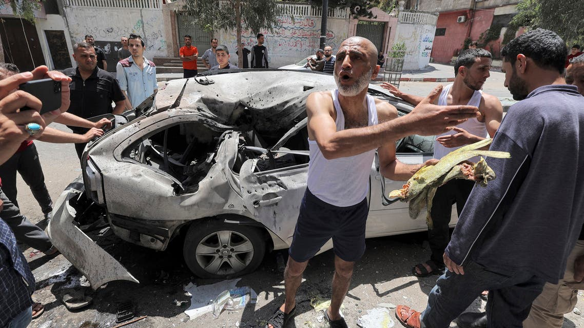 Palestinians inspect a vehicle destroyed by an Israeli air strike after the bodies of its passengers and driver were retrieved, in Gaza City on May 12, 2021.