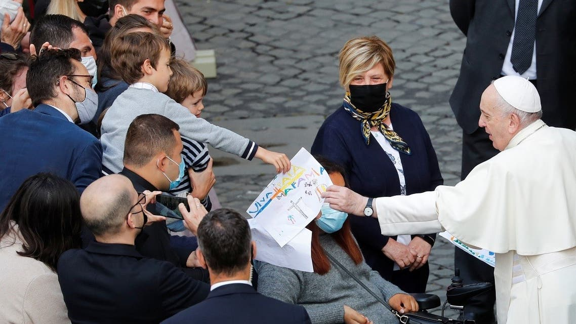 Pope Francis receives a drawing from a child as he arrives for the weekly general audience while coronavirus disease (COVID-19) restrictions are eased at the Vatican, on May 12, 2021. (Reuters)