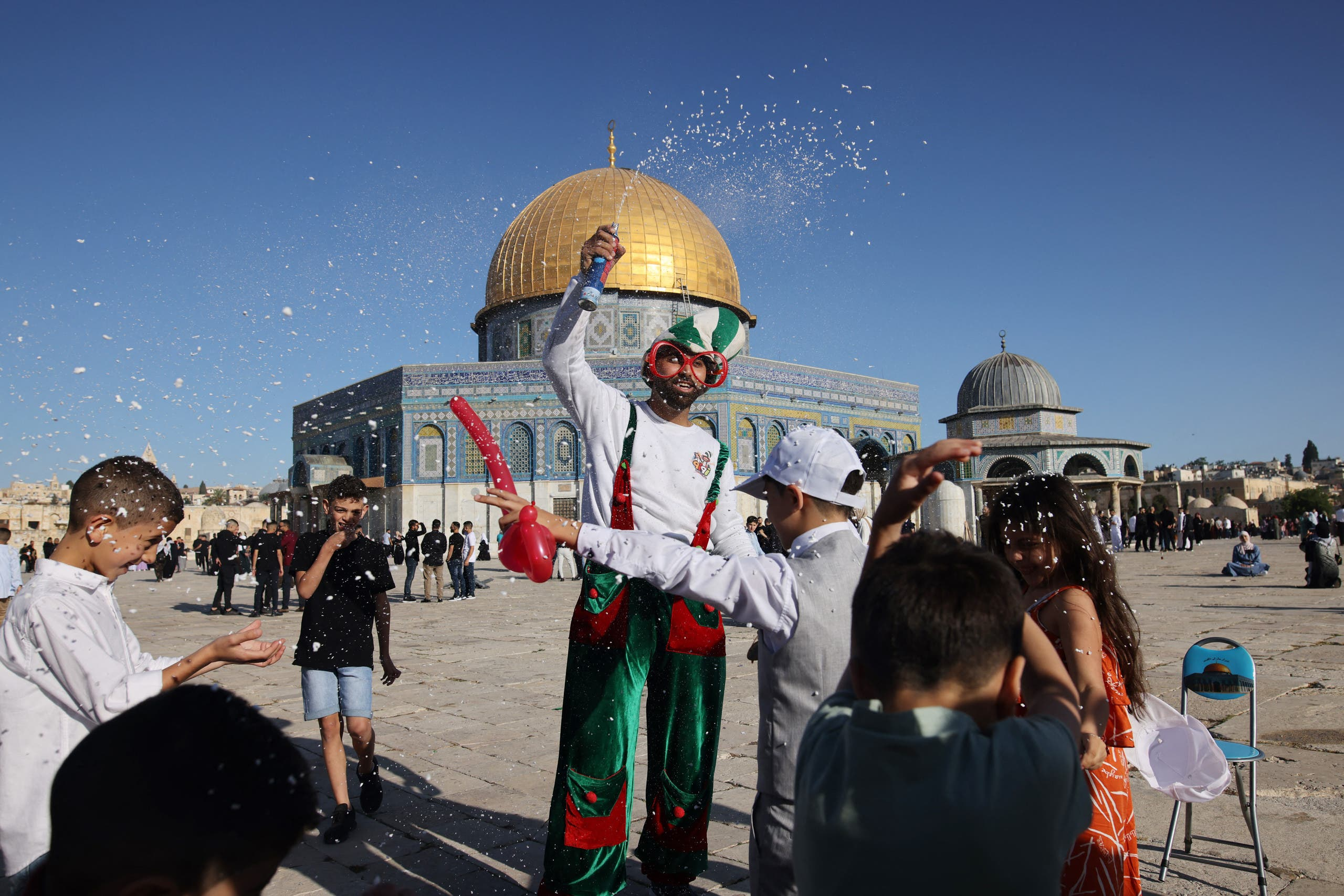 Muslim children celebrate in front of the Dome of the Rock mosque after the morning Eid al-Fitr prayer at the al-Aqsa mosques compound in Old Jerusalem early on May 13, 2021. (AFP)