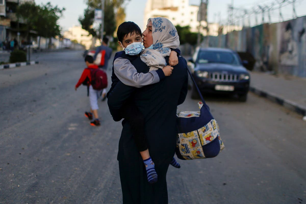A Palestinian woman carrying her son evacuates after their tower building was hit by Israeli air strikes, amid a flare-up of Israeli-Palestinian violence, in Gaza City May 12, 2021. (Reuters)