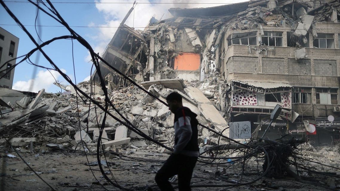 A Palestinian man walks past the remains of a tower building which was destroyed in Israeli air strikes in Gaza City May 13, 2021. (Reuters)