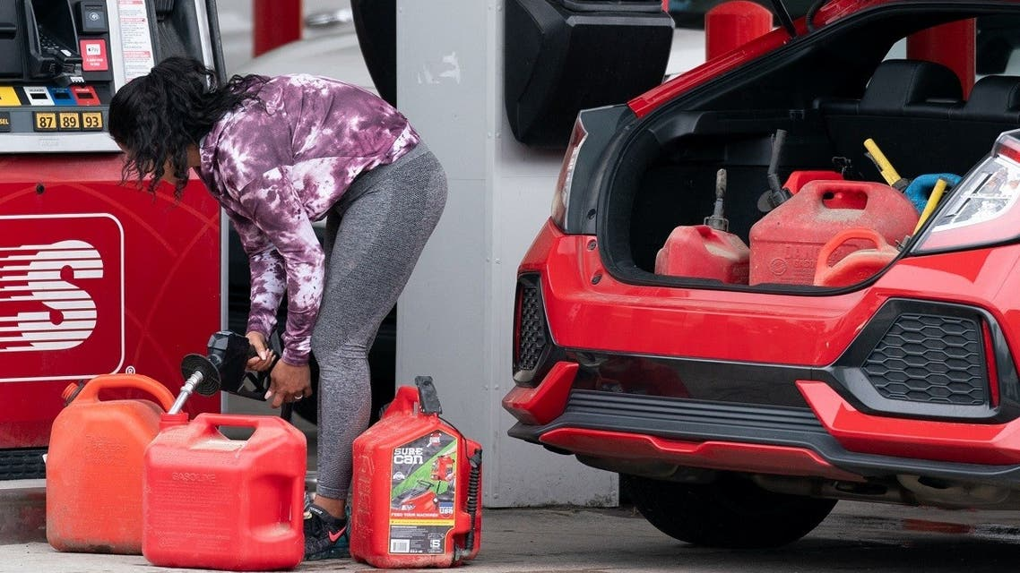 A woman fills gas cans at a Speedway gas station on May 12, 2021 in Benson, North Carolina. (AFP)