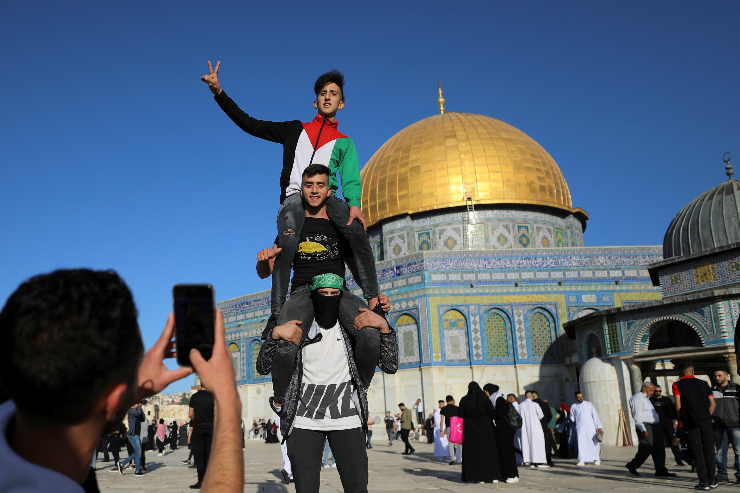 Palestinian youths pose as a friend photographs them, while the Dome of the Rock is seen in the background, during Eid al-Fitr prayers, which mark the end of the holy fasting month of Ramadan, at the compound that houses al-Aqsa mosque on May 13, 2021. (Reuters)
