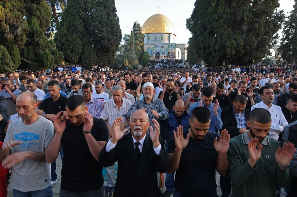 Muslims perform the morning Eid al-Fitr prayer, marking the end of the holy fasting month of Ramadan, outside the Dome of the Rock mosque in the al-Aqsa mosques compound in Old Jerusalem early on May 13, 2021. (AFP)