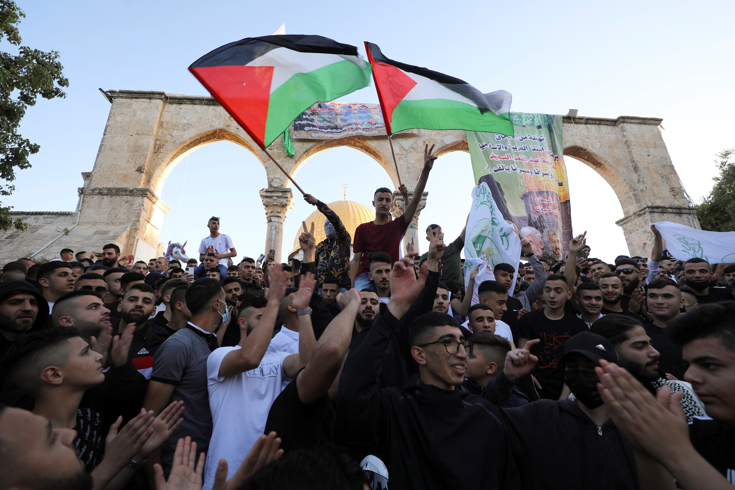 People wave Palestinian flags during Eid al-Fitr prayers, which mark the end of the holy fasting month of Ramadan, at the compound that houses al-Aqsa mosque on May 13, 2021. (Reuters)