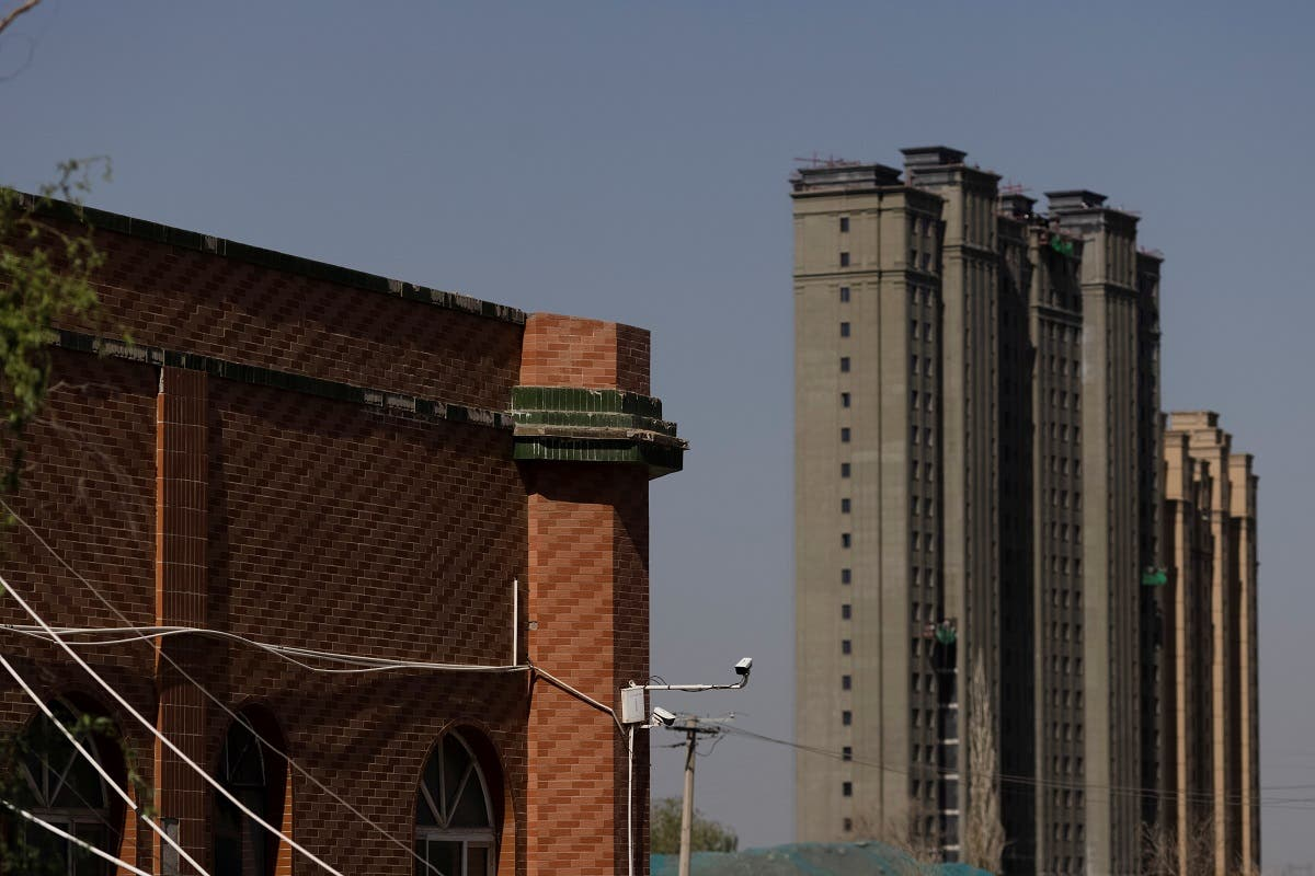 Apartment towers rise behind the former Xinqu Mosque that had its minarets removed in Changji outside Urumqi, Xinjiang Uyghur Autonomous Region, China, May 6, 2021. (Reuters)