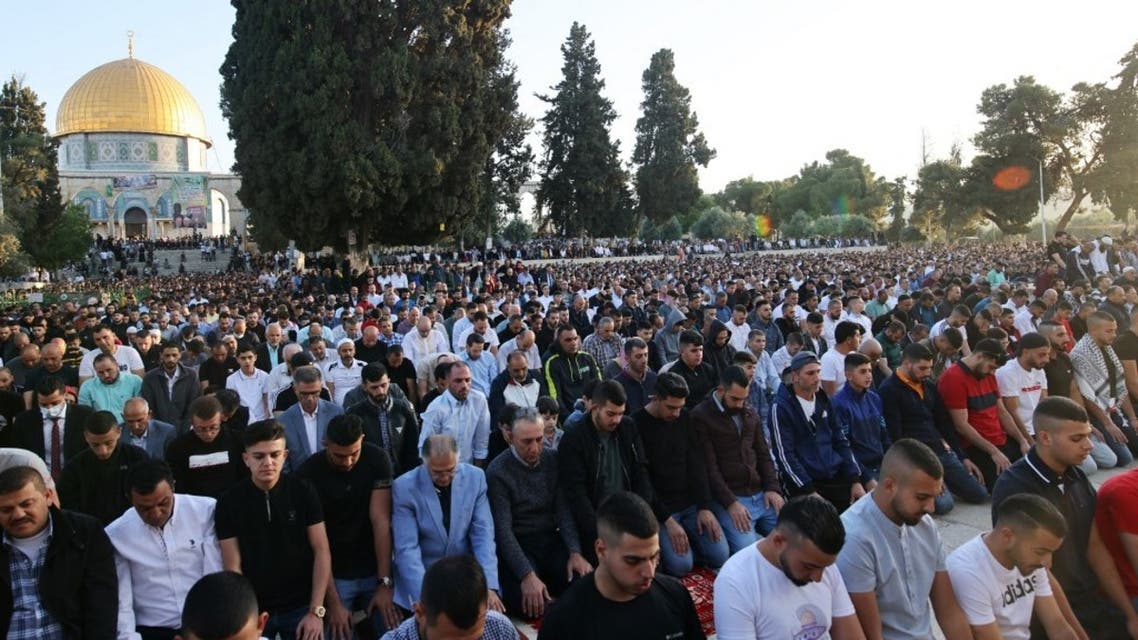 Muslims perform the morning Eid al-Fitr prayer, marking the end of the holy fasting month of Ramadan, outside the Dome of the Rock mosque in the al-Aqsa mosques compound in Jerusalem early on May 13, 2021. (AFP)