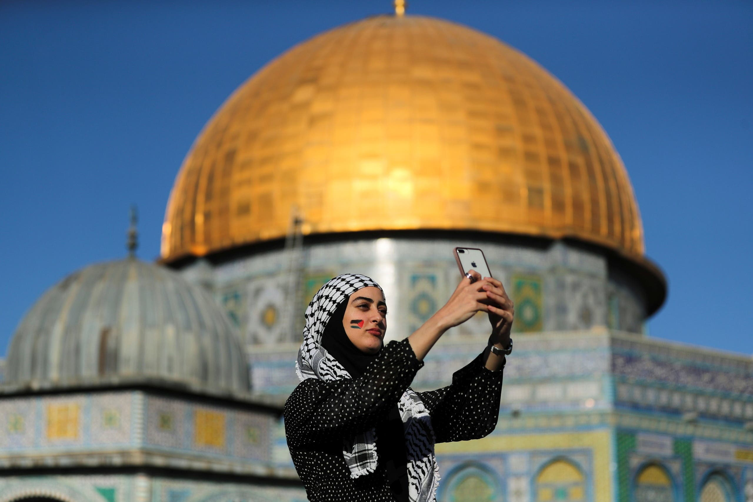 A Palestinian woman takes a selfie as the Dome of the Rock is seen in the background, during Eid al-Fitr prayers on May 13, 2021. (Reuters)