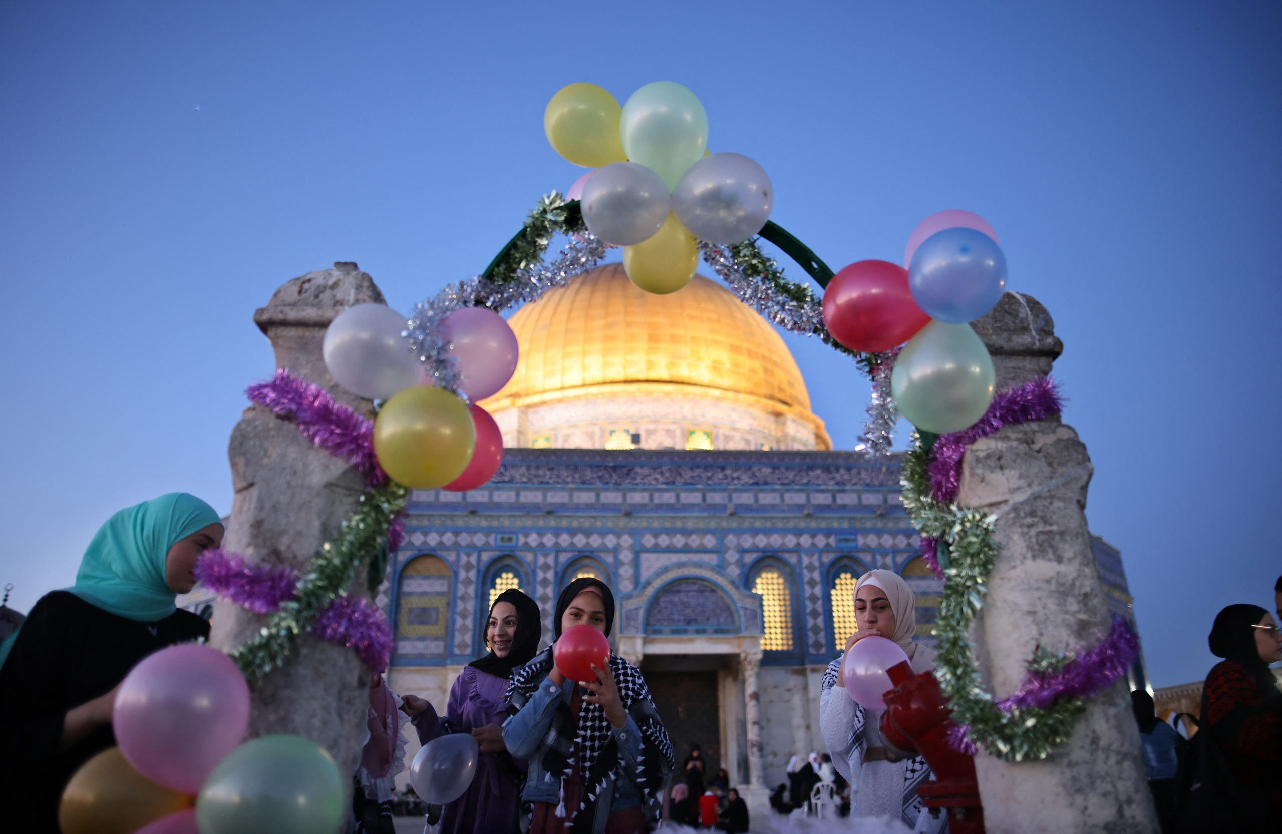 Muslim women blow up balloons as worshippers celebrated the Eid al-Fitr holiday, which marks the end of the holy fasting month of Ramadan, after the morning prayer at the al-Aqsa mosques compound, with the Dome of the Rock mosque in the background, in Old Jerusalem early on May 13, 2021. (AFP)