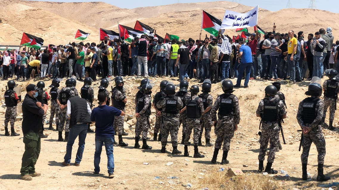 Demonstrators hold Palestinian flags during a protest to express solidarity with the Palestinian people, in Karameh, Jordan valley, Jordan May 14, 2021. (Reuters)