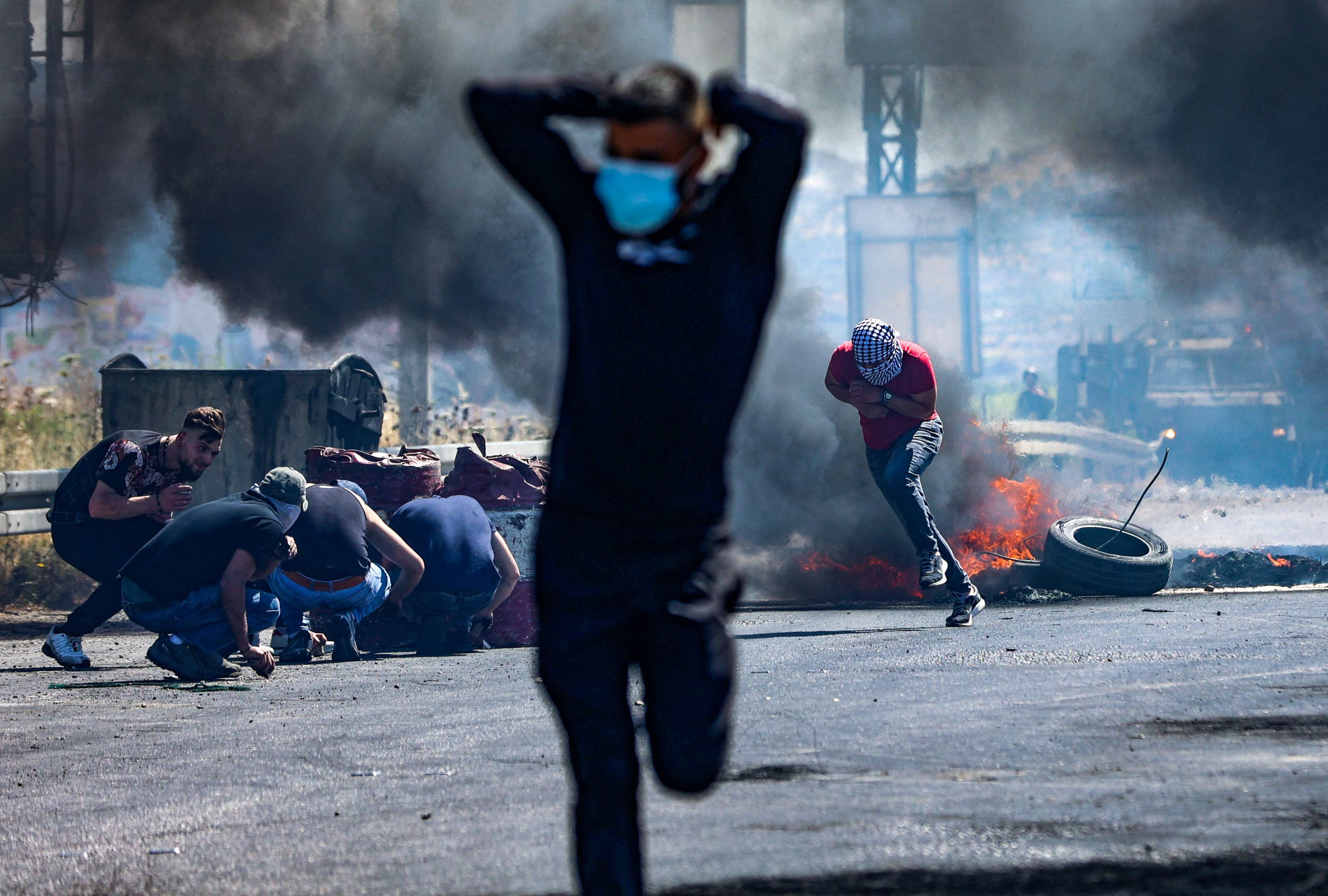 Palestinians run as others take cover, during confrontations with Israeli security forces near the Hawara checkpoint south of the occupied West Bank city of Nablus, on May 14, 2021. (AFP)