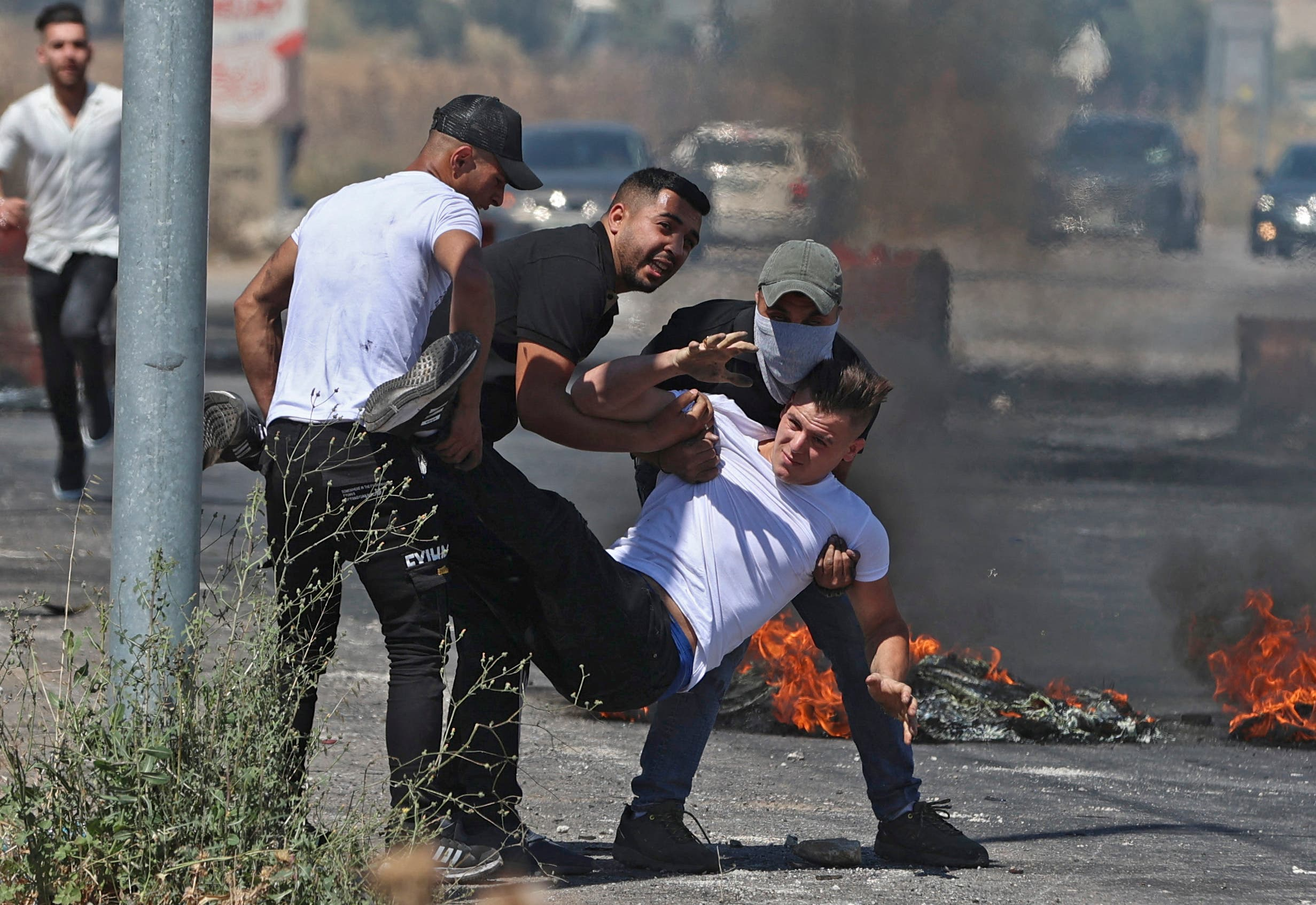 Palestinians carry an injured man to safety, after Israeli security forces launch attacks near the Hawara checkpoint south of the occupied West Bank city of Nablus, on May 14, 2021. (AFP)