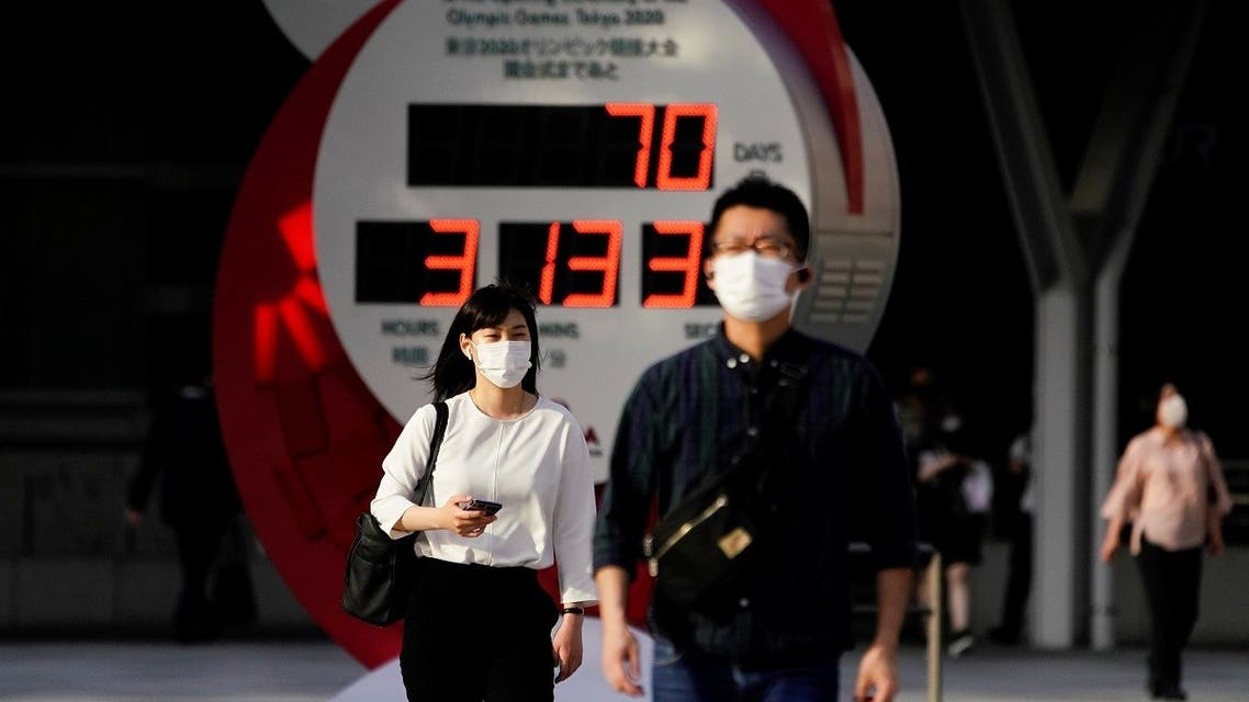 Passersby wearing protective face masks walk near a countdown clock of Tokyo 2020 Olympic Games that have been postponed to 2021 due to the coronavirus outbreak, in Tokyo, Japan, on May 14, 2021. (Reuters)