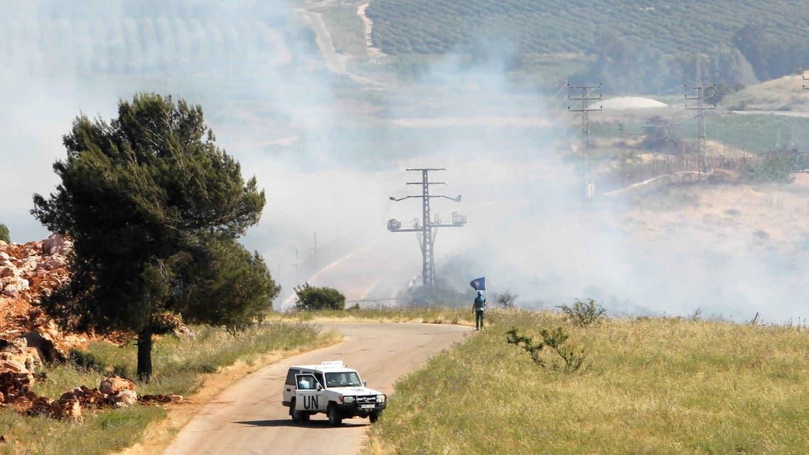 أحد أفراد اليونيفيل يقف أثناء تصاعد الدخان في بلدة الخيام قرب الحدود مع اسرائيل الجمعة (رويترز)