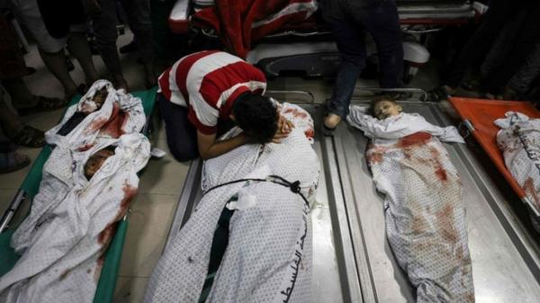 صور مروعة.. فلسطيني ينتحب فوق جثث 10 من أسرة واحدة