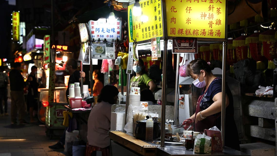 A woman wearing a protective face mask prepares food at her stall during the coronavirus disease (COVID-19) pandemic, in Taipei, Taiwan, May 11, 2021. (Reuters)