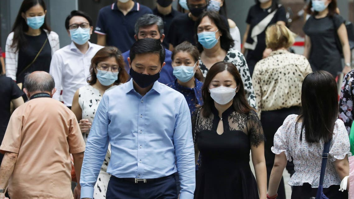 Office workers wearing masks cross a street during lunch hour, amid the coronavirus disease (COVID-19) outbreak, in Singapore May 12, 2021. (Reuters)