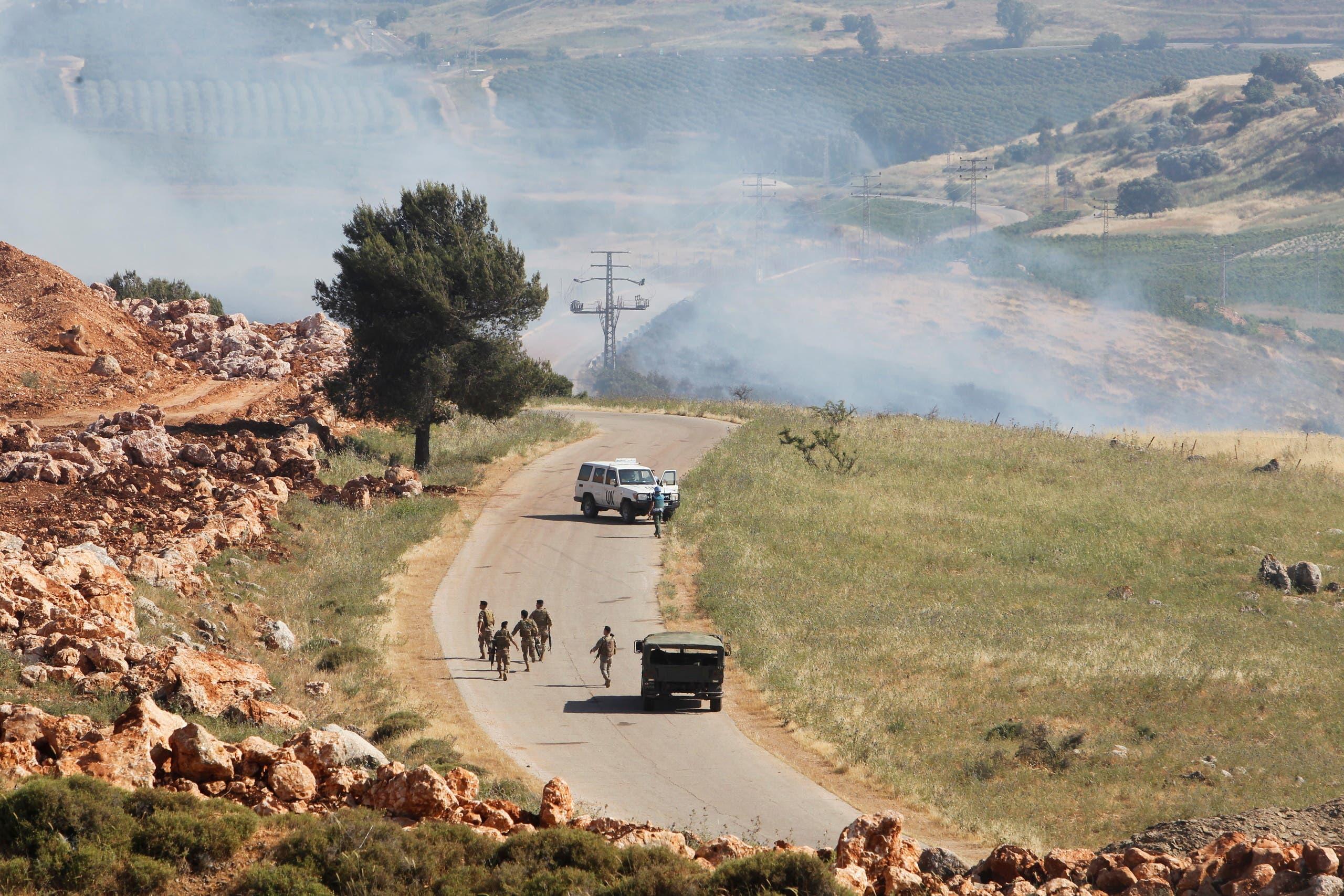 جنود لبنانيون يسيرون مع تصاعد الدخان في قرية الخيام جنوباً بالقرب من الحدود مع إسرائيل الجمعة (رويترز)