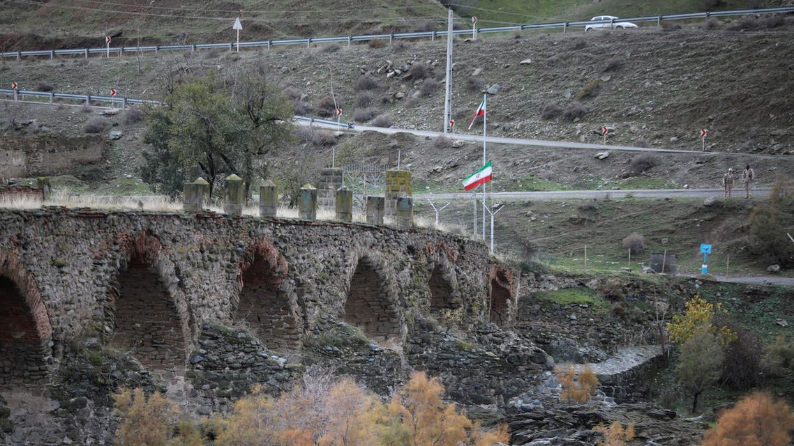 A view shows the ancient Khodaafarin Bridge near the border with Iran in the area, which came under the control of Azerbaijan's troops following a military conflict over Nagorno-Karabakh against ethnic Armenian forces and a further signing of a ceasefire deal, with Iranian service members seen in the background, in Jabrayil District, December 7, 2020. Picture taken December 7, 2020. REUTERS/Aziz Karimov