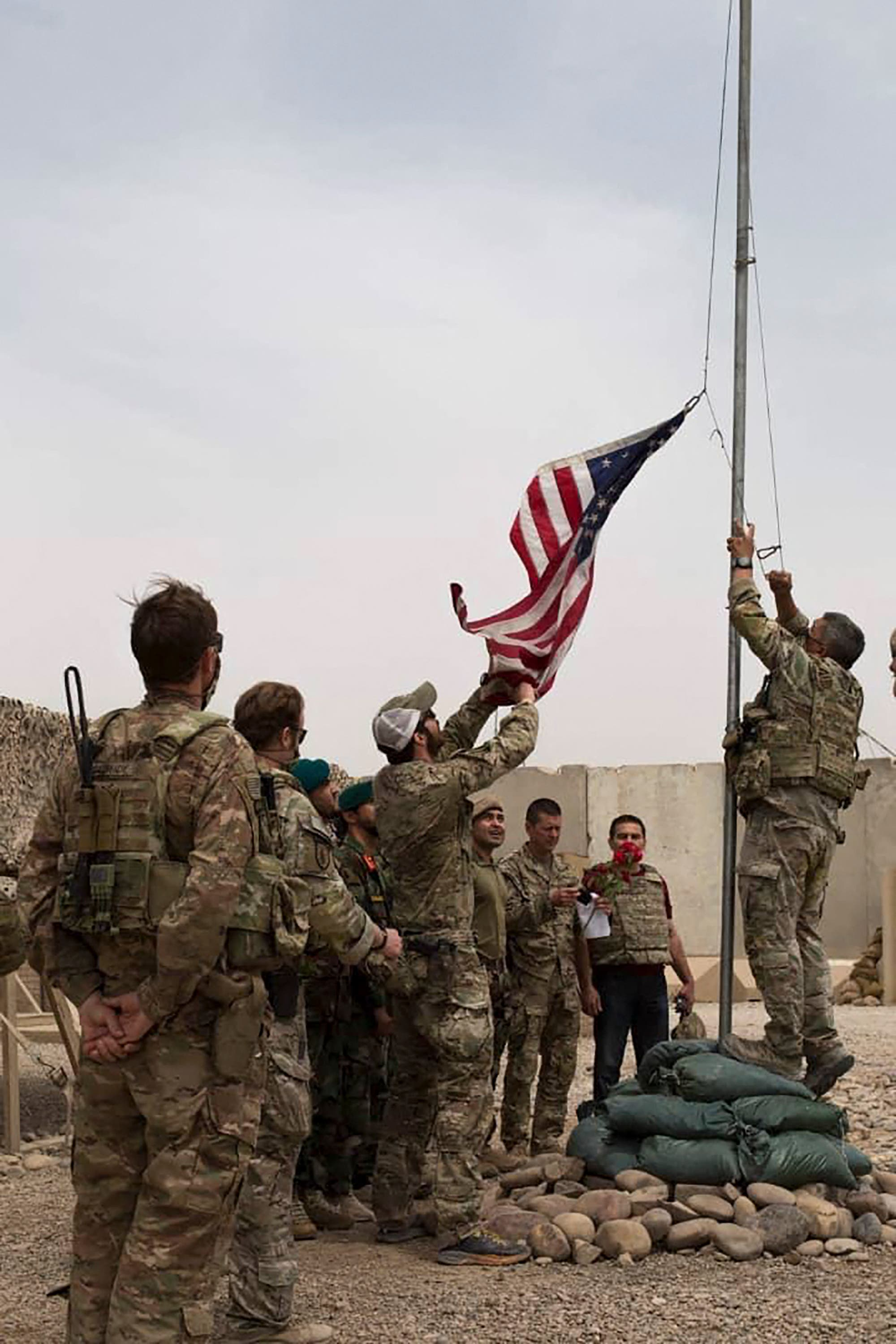 US soldiers lowering the US national flag during a handover ceremony to the Afghan National Army (ANA) army 215 Maiwand corps at Antonik camp in Helmand province. (File photo)