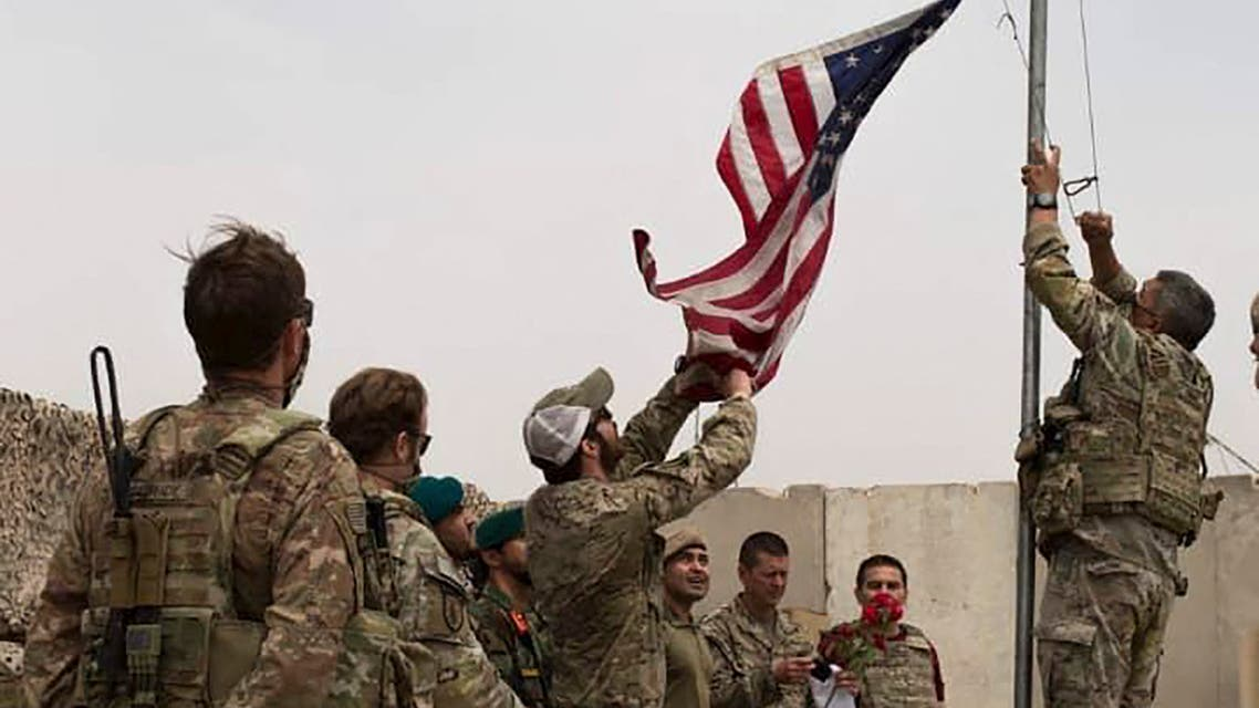 This handout photograph taken on May 2, 2021 and released by Afghanistan's Ministry of Defense shows US soldiers lowering the US national flag during a handover ceremony to the Afghan National Army (ANA) army 215 Maiwand corps at Antonik camp in Helmand province.