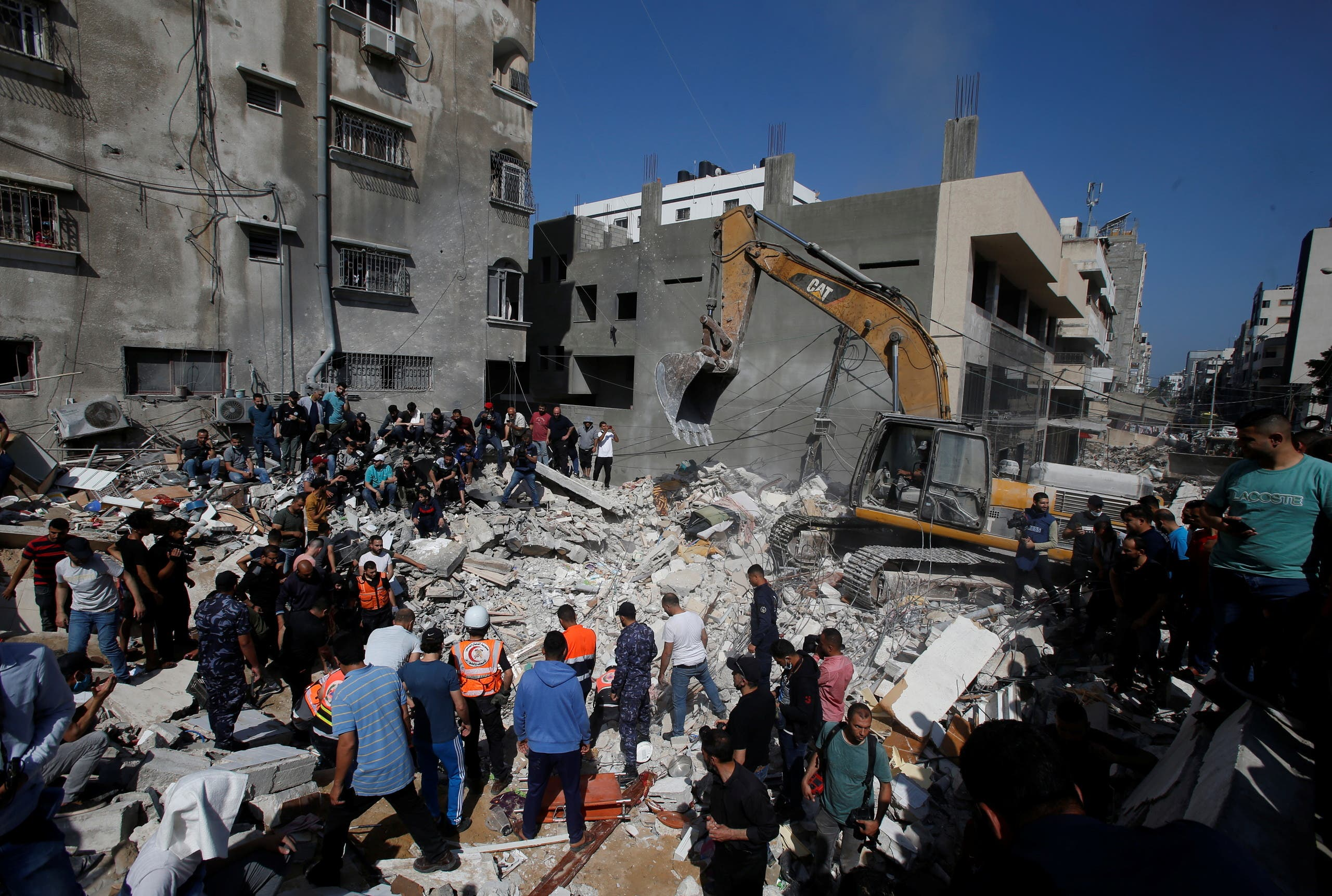 Rescue workers search for victims amid rubble at the site of Israeli air strikes, in Gaza City May 16, 2021. (Reuters)