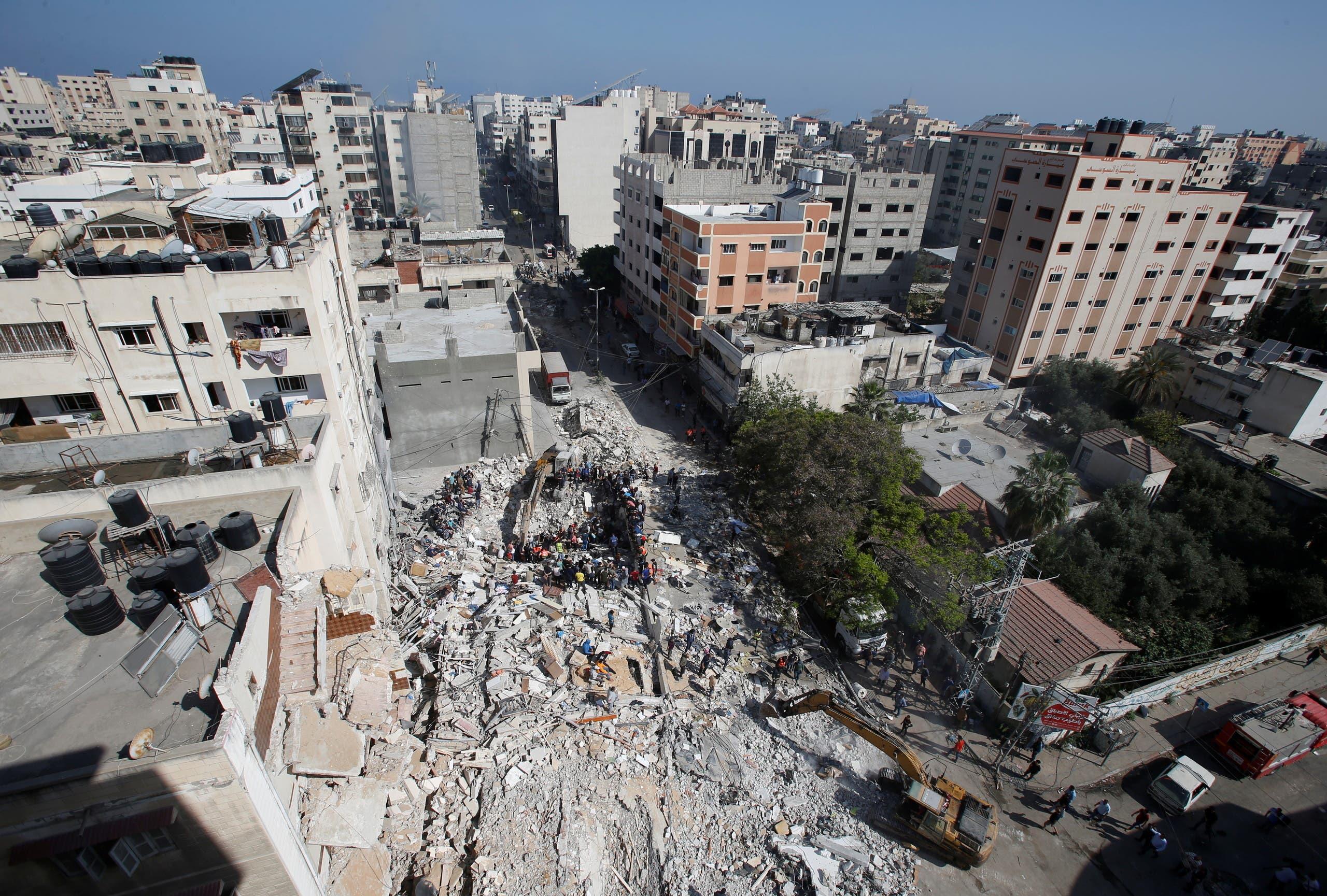 البحث عن جثث تحت أنقاض مبنى تهدم في غزة بفعل القصف الإسرائيلي