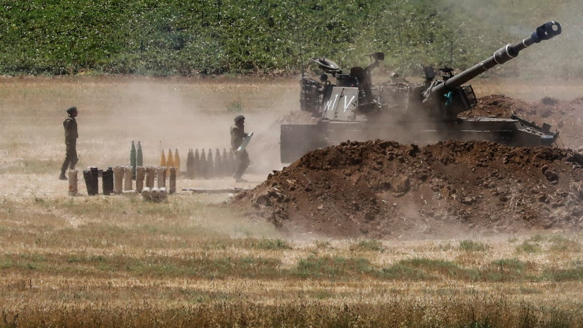 An Israeli soldier carries a shell near a military artillery unit, as seen from the Israeli side of the border with the Gaza Strip May 16, 2021. REUTERS/Baz Ratner