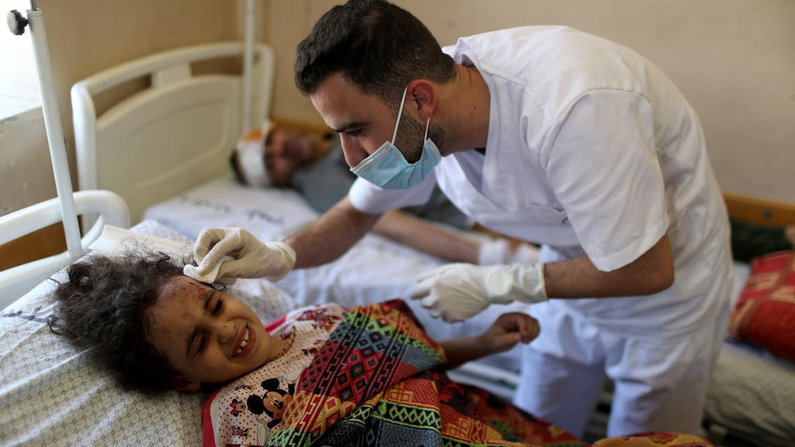 Palestinian girl Suzy Eshkuntana, 6, is treated by a medic at a hospital after being pulled from the rubble of a building amidst Israeli air strikes, in Gaza City May 16, 2021. REUTERS/Mohammed Salem SEARCH SUZY ESHKUNTANA FOR THIS STORY. SEARCH WIDER IMAGE FOR ALL STORIES.