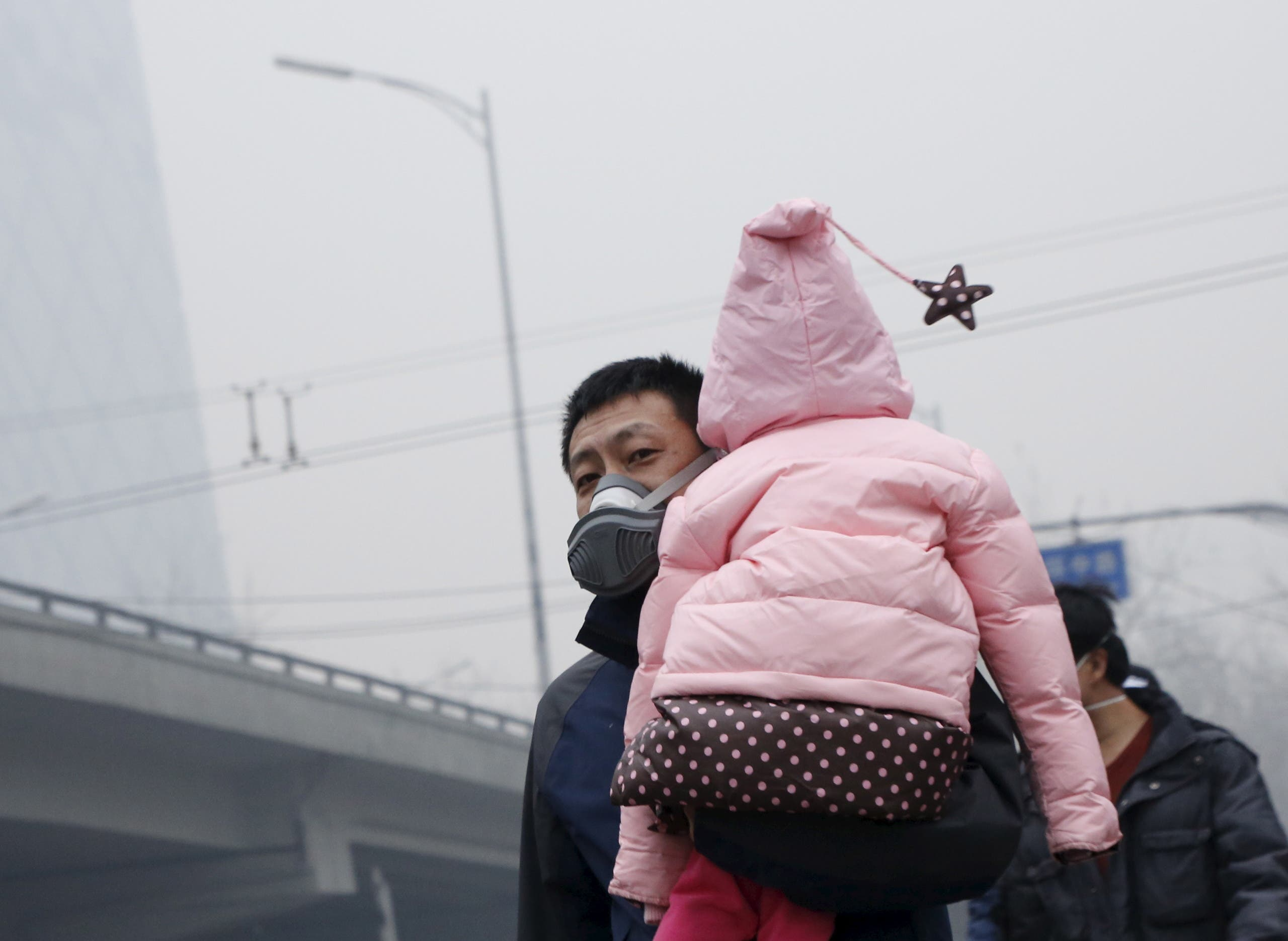 A man wearing a mask carries his baby on his shoulder amid heavy smog after the city issued its first ever red alert for air pollution, in Beijing, China, December 8, 2015. (File photo: Reuters)