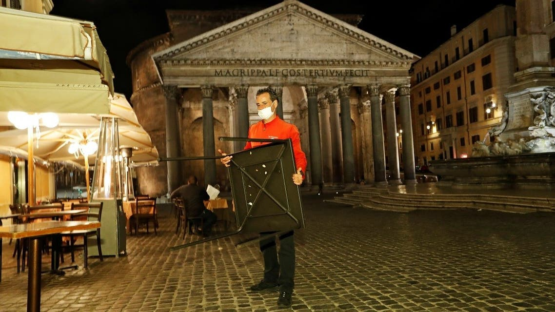 A man removes a table from a square in front of the Pantheon before a curfew imposed by the region of Lazio from midnight to 5 a.m to curb the coronavirus disease (COVID-19) infections in Rome, Italy, October 23, 2020. (Reuters)