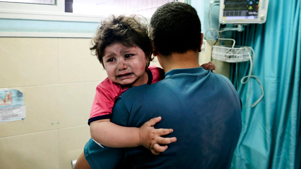A Palestinian man holds an injured girl awaiting medical care at al-Shifa hospital, after an Israeli air strike in Gaza city, on May 11, 2021. (AFP)